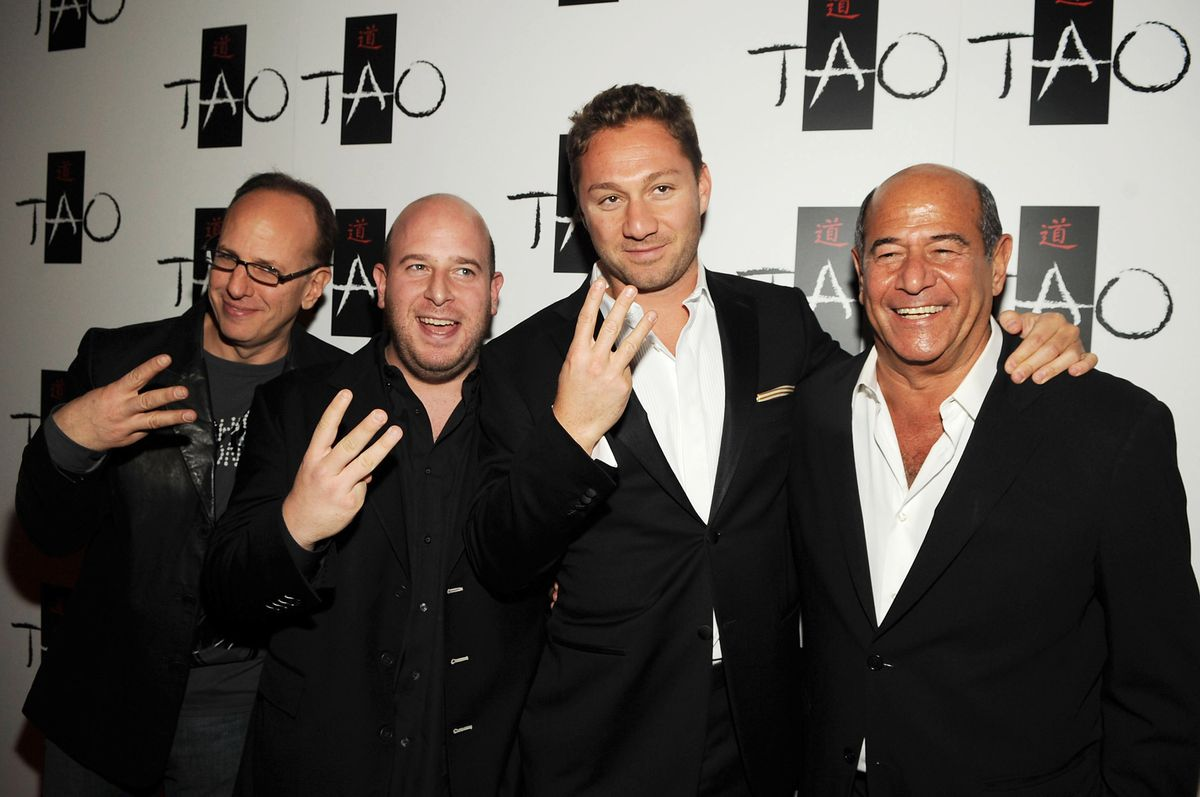 Rich Wolf, Noah Tepperberg, Jason Strauss, and Marc Packer, all wearing suits and holding up three fingers in front of a TAO backdrop.