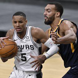 San Antonio Spurs' Dejounte Murray (5) drives around Utah Jazz's Rudy Gobert during the second half of an NBA basketball game, Sunday, Jan. 3, 2021, in San Antonio.
