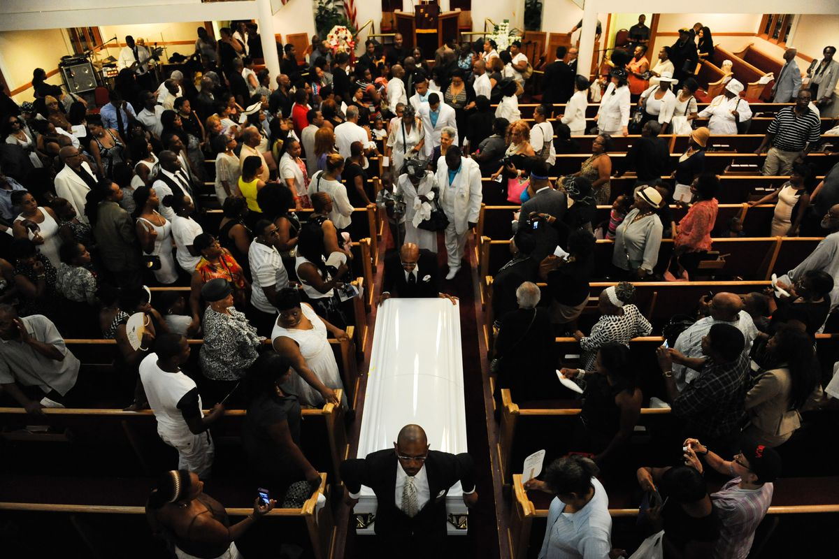 Mourners watch as Eric Garner's coffin is carried out of Bethel Baptist Church