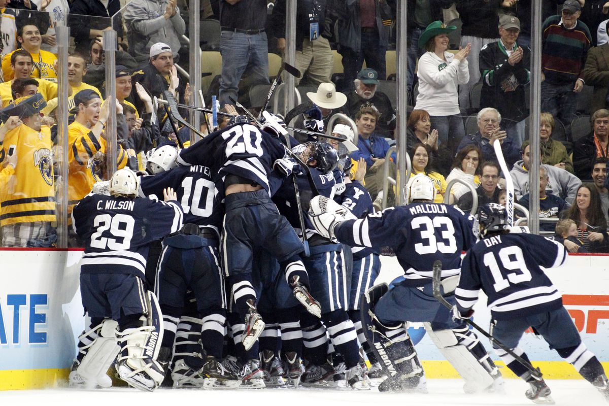 Yale players mob senior captain Andrew Miller following his overtime game-winning goal against UMass Lowell.