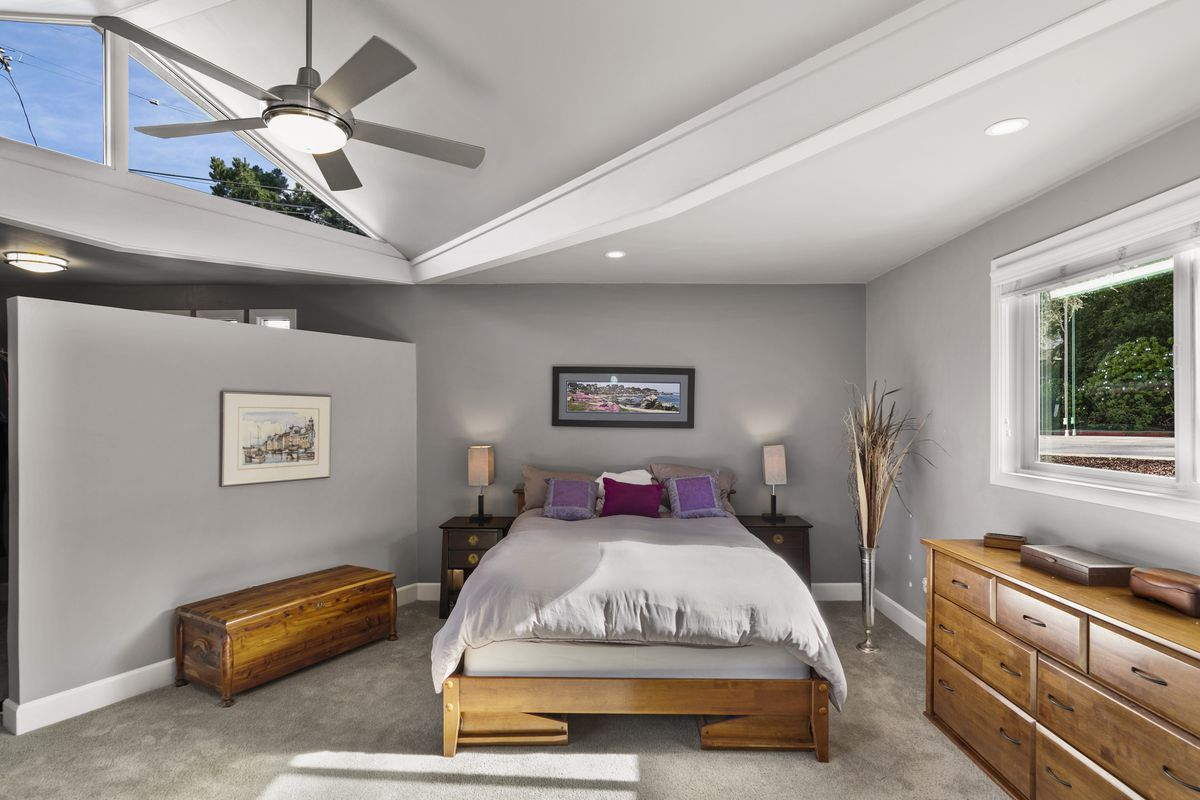 A gray queen size bed sits in a master bedroom that has gray walls and white trim.