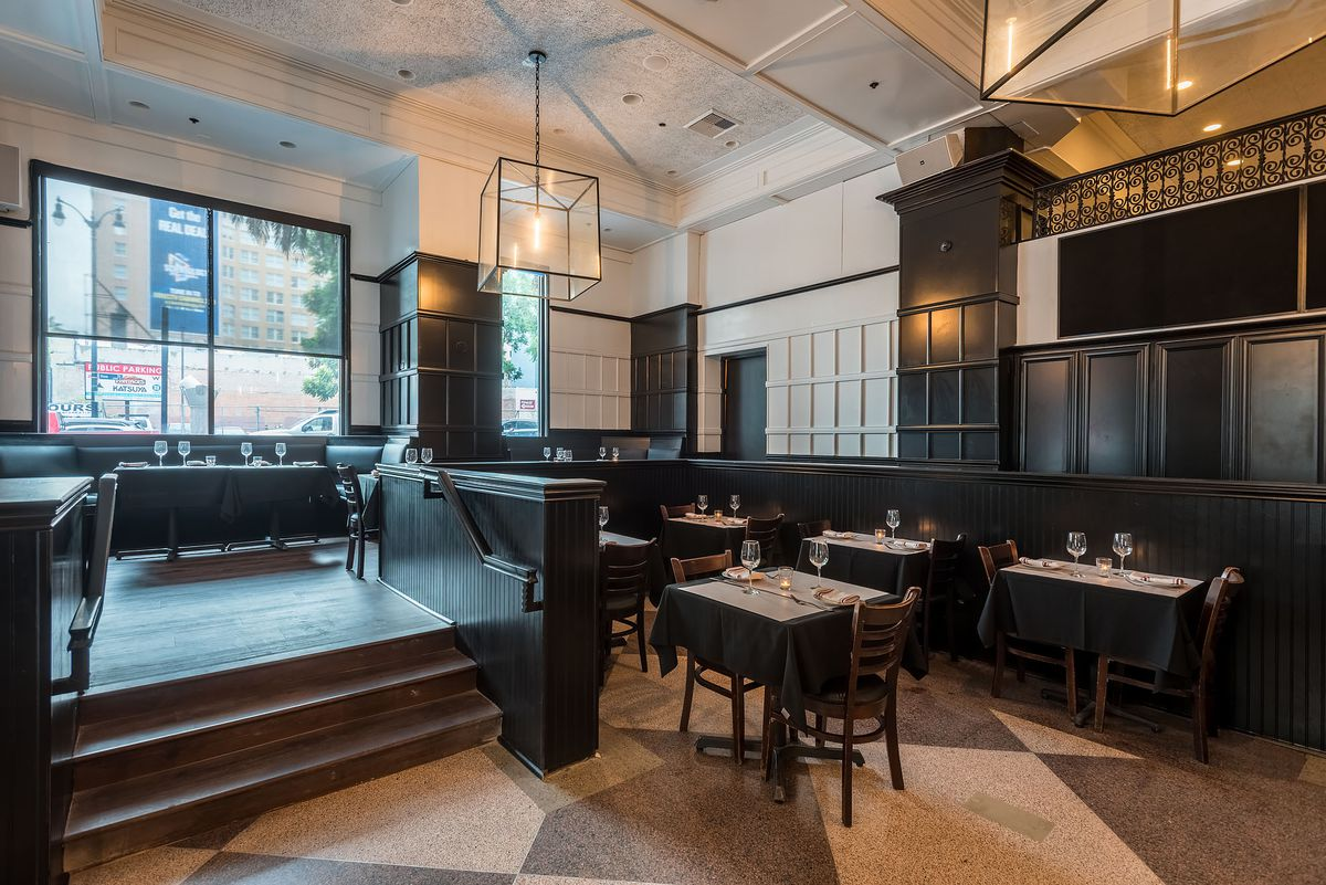 Small tables and light fixtures inside a new Italian restaurant.