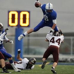 Bingham defensive back Braden Andersen leaps over a Jordan player in a playoff game last year. Anderson is one of five returning starters for the Miners this year.