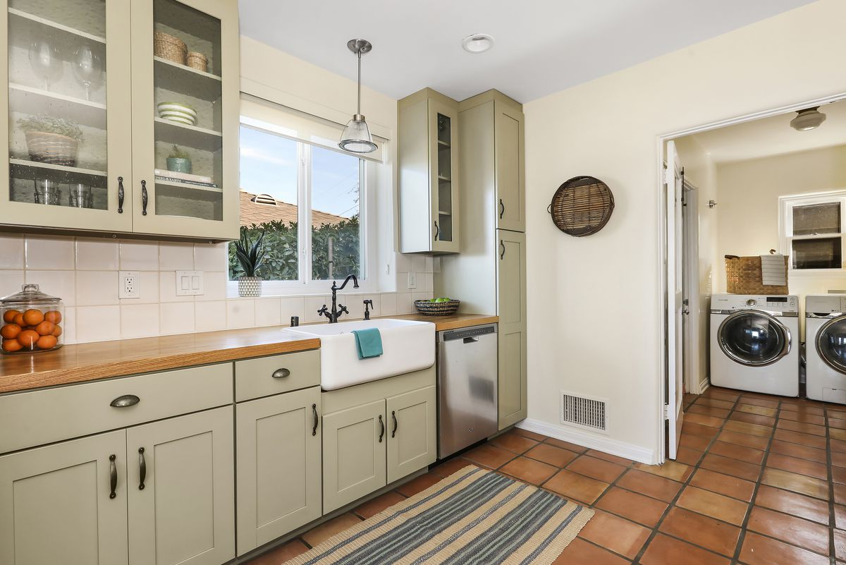 A kitchen with butcher block counters, a farmhouse sink, and ceramic tile floors.