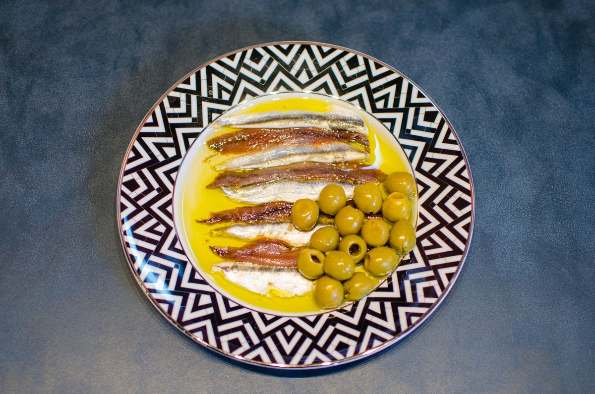 Overhead view of a plate of brown and white anchovies lined up in a pool of olive oil, with a pile of green olives on the side. The plate has a black and white zigzag pattern around the edge, and it sits on a slate blue surface.