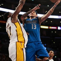 Dallas Mavericks shooting guard Delonte West attempts a shot over Los Angeles Lakers center Andrew Bynum during the first half of an NBA basketball game, Sunday, April 15, 2012, in Los Angeles.