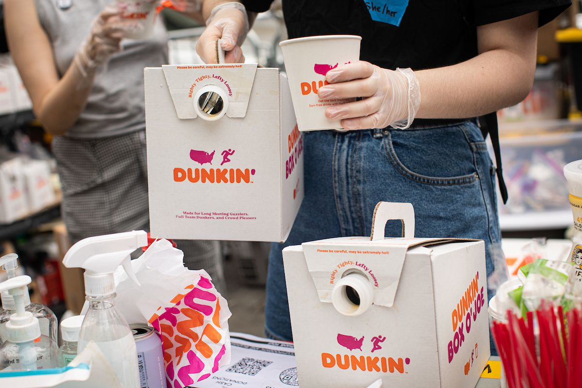 A person in jeans and a black t-shirt holds a reusable paper cup in a hand with plastic gloves. In their other hand, they hold a large container of Dunkin Donuts coffee.