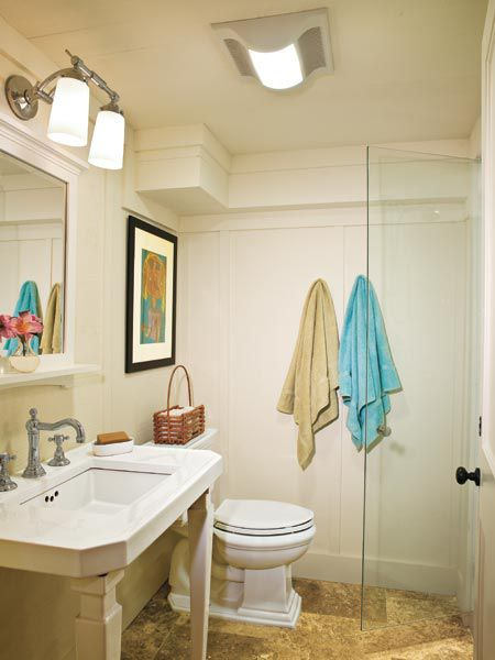 White pedestal sink with a mirror above it.