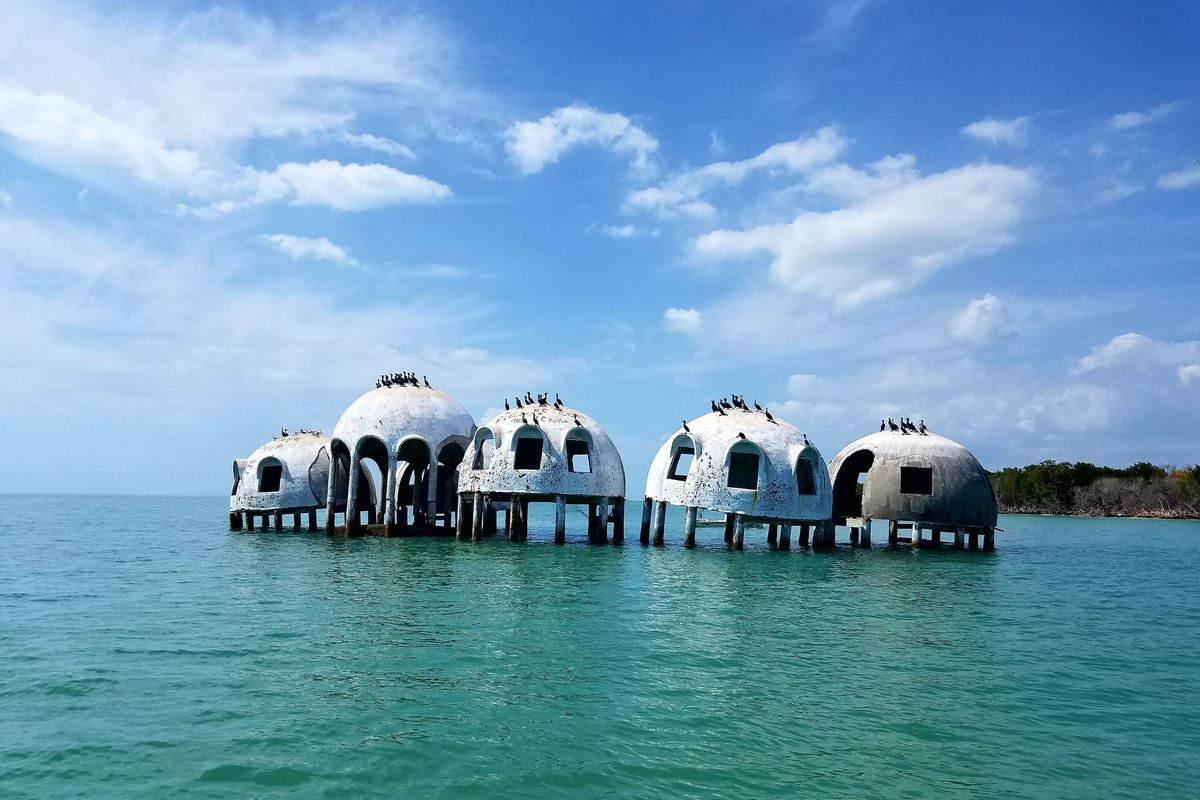 A series of dilapidated dome structures sit in blue green water with blue skies overhead.
