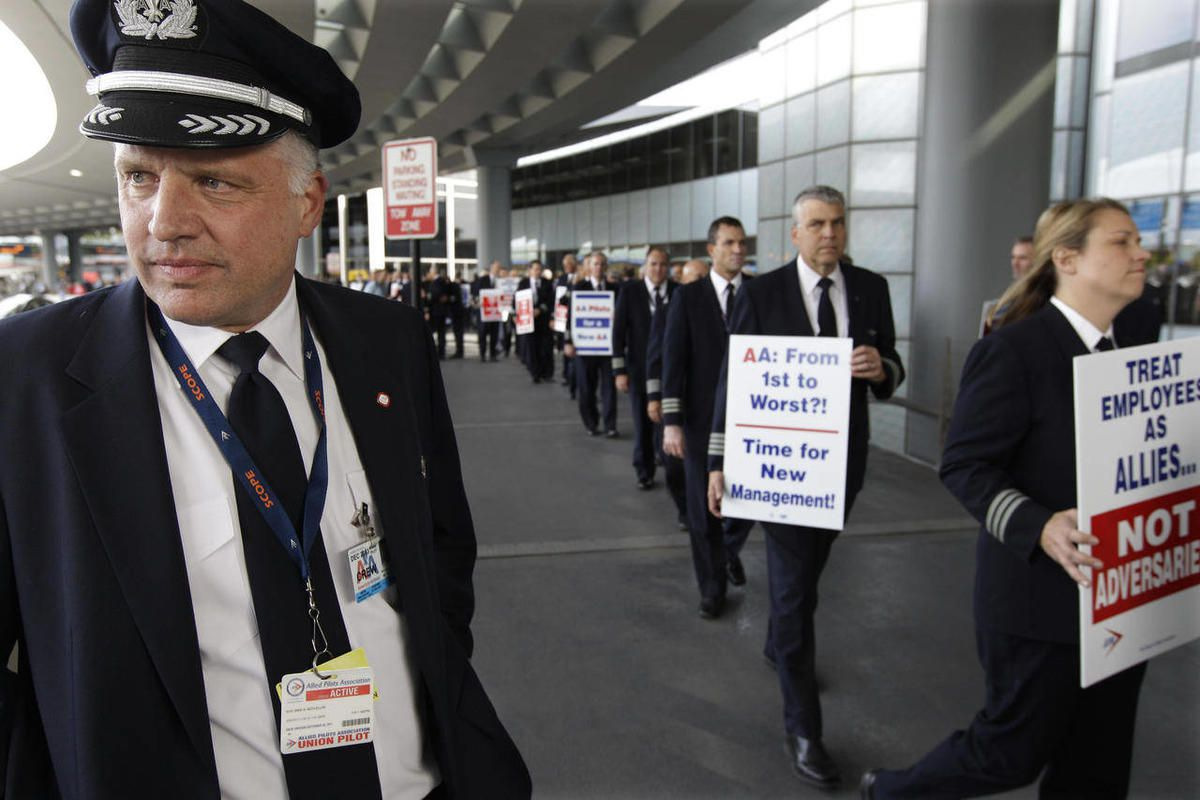 FILE- In this Thursday, Sept. 20, 2012, file photo, Captain Mike McClellan, ORD Domicile Chairman of the Allied Pilots Association left, joins over 200 American Airline pilots marching on a picket line at O'Hare International Airport, in Chicago. There co