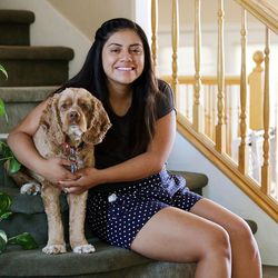 Stephanie Pesantes, who traveled to Washington, D.C., to meet with Michelle Obama, poses for a portrait with the family dog Teddy in Salt Lake City, Tuesday, July 28, 2015.