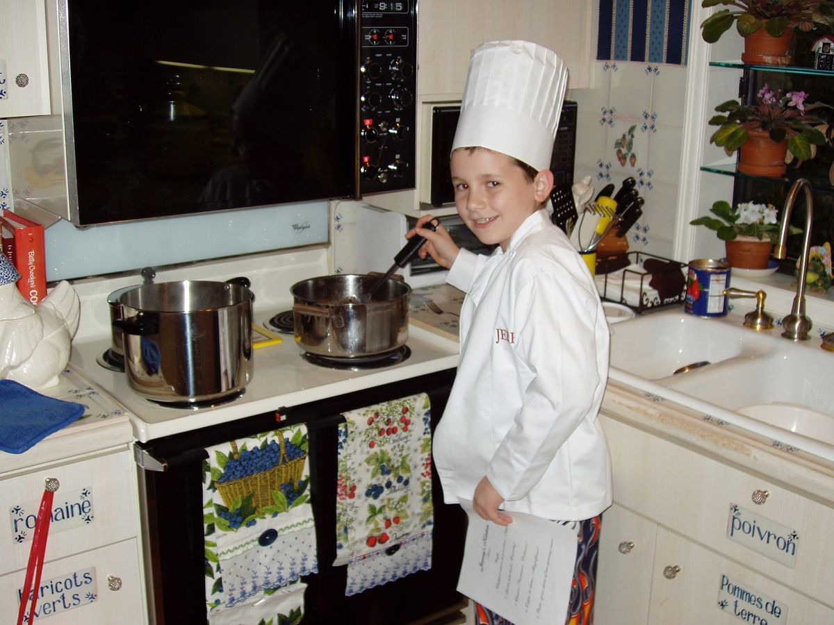 Kid at stove wearing chefs whites