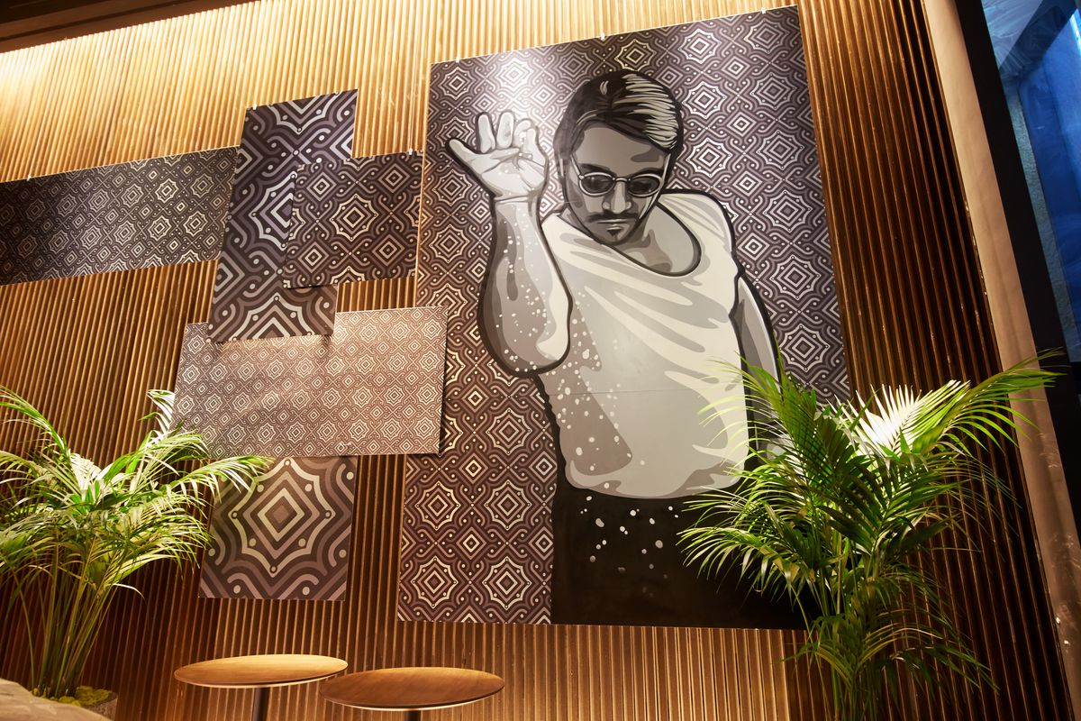 A photograph of a mural on a wall depicting a man in a white t-shirt, black pants, and sunglasses sprinkling salt over an imaginary steak