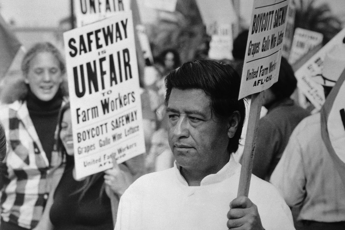 Cesar Chavez is seen leading a strike in a black-and-white photo.
