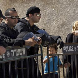 Palestinian Maisus Al-Ghawy, right, stands with her son Adam next to Israeli police officers after being evicted earlier from her house in the East Jerusalem neighborhood of Sheikh Jarrah Sunday.