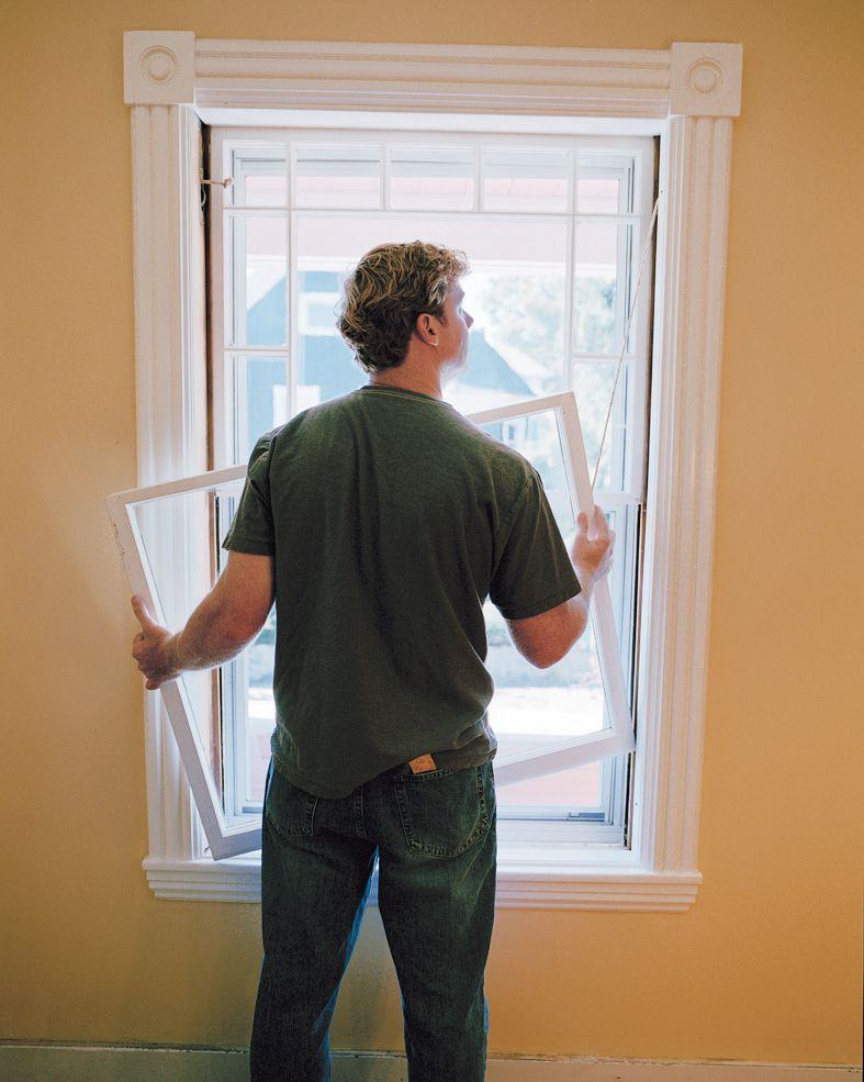 Person taking out lower sash from double hung window to prepare to seal it.