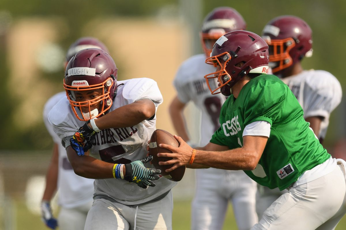 Brother Rice quarterback Jack Lausch (8) fakes to running back Aaron Vaughn (5) during practice.