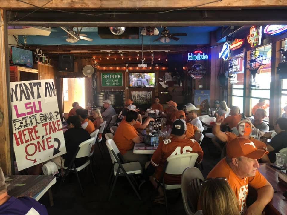 People in orange shirts at a bar