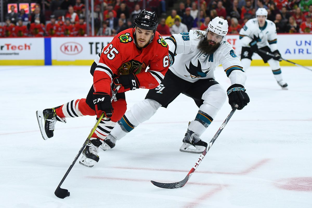 Andrew Shaw #65 of the Chicago Blackhawks advances the puck under pressure from Brent Burns #88 of the San Jose Sharks during the second period of the home opening game at United Center on October 10, 2019 in Chicago, Illinois.