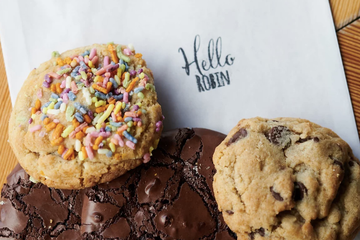 A selection of cookies: one with rainbow sprinkles, one that's dark chocolate, and one chocolate chip variety