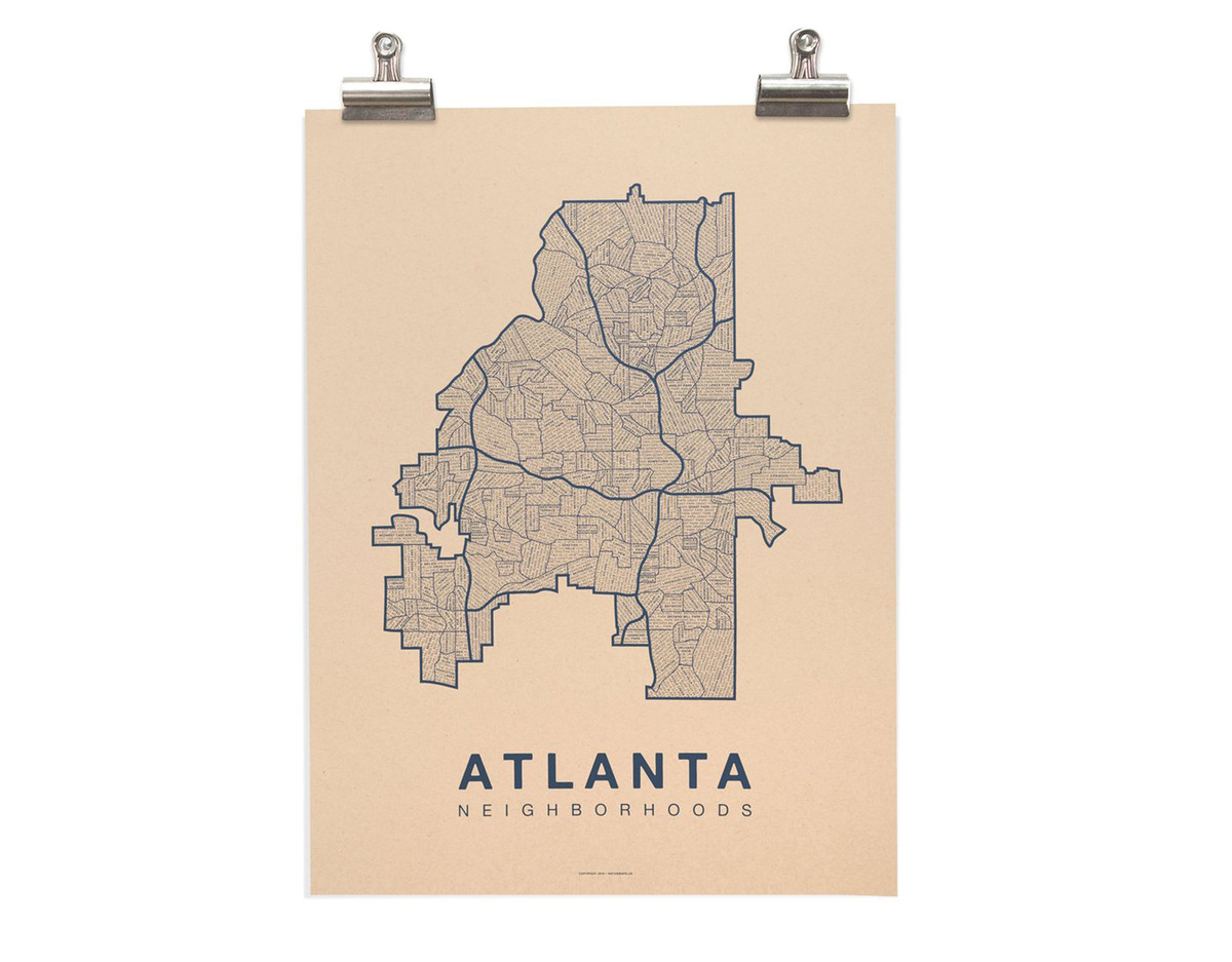 A map hangs on a white wall. The map has words written on it which read: Atlanta neighborhoods.