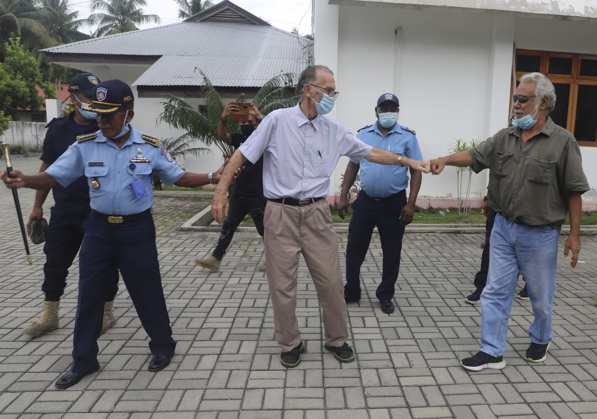 Xanana Gusmao (right), former East Timorese president and prime minister, gives a fist bump to Richard Daschbach (center), a defrocked priest on trial on child abuse charges, after a hearing at a courthouse in Oecusse, East Timor on Feb. 23. Daschbach's support appears deep and widespread, extending beyond Oecusse to the capital city of Dili. It includes members of the political elite, including Gusmao.