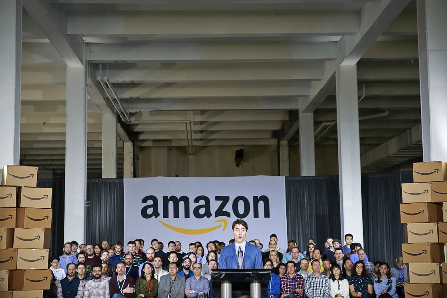 Canadian Prime Minister Justin Trudeau standing at a podium in front of an Amazon banner and a crowd of people while announcing a new tech hub in Vancouver.