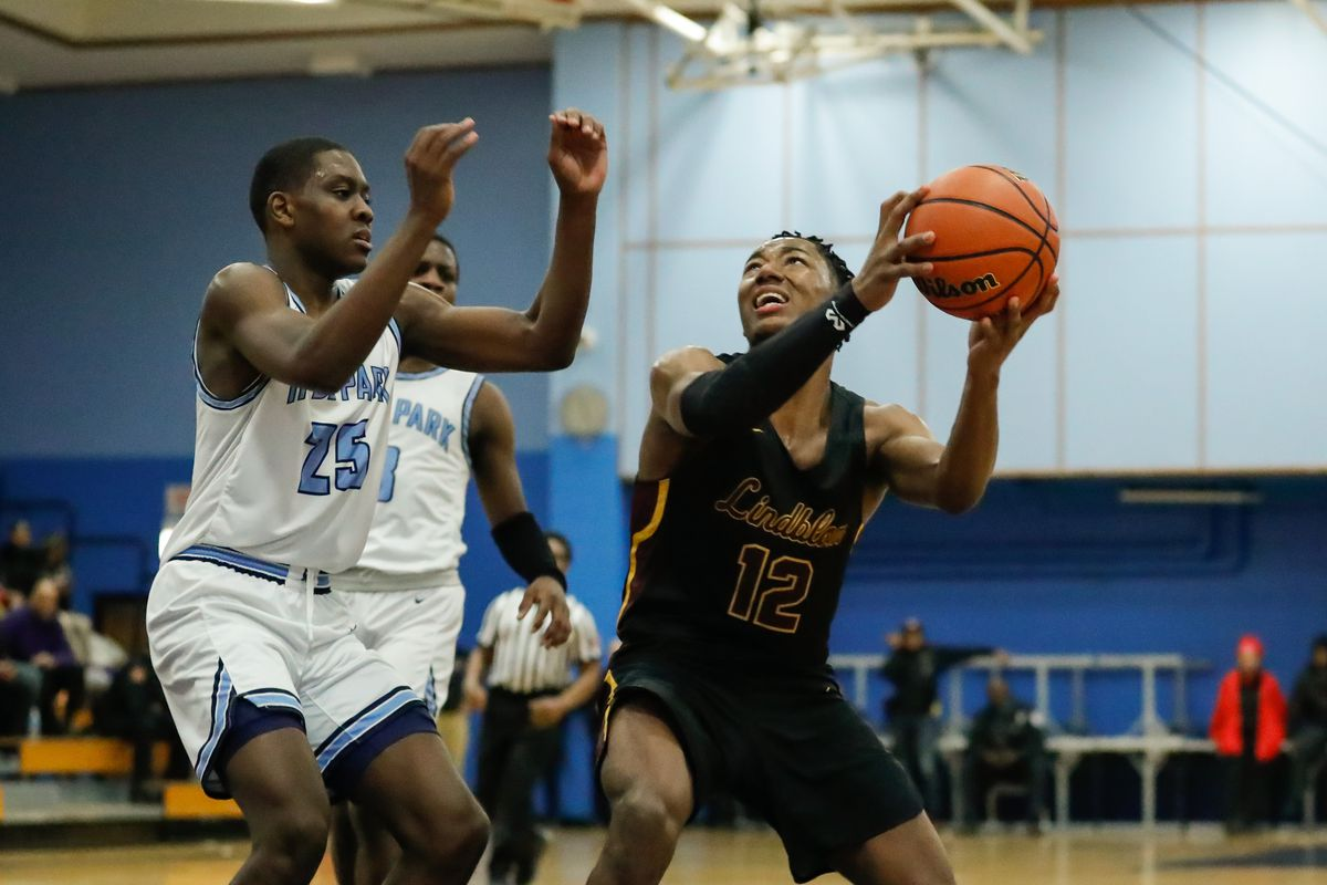 Lindblom's Myles Twyman (12) takes the ball to the basket against Hyde Park.