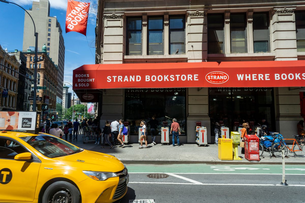 """A historic building with a red awning on its exterior. The awning reads """"Strand Bookstore."""""""