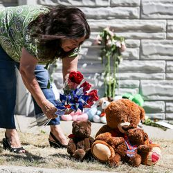 Jodie Ferguson, who said she lives just a few houses away, adds several roses and pinwheels to a memorial to the victims of Tuesday's fatal shooting on Alta Canyon Drive in Sandy on Wednesday, June 7, 2017.