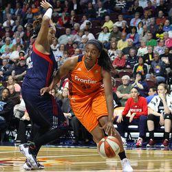 Connecticut Sun's Morgan Tuck (33) drives past Washington Mystics' Tianna Hawkins (21) to the basket.