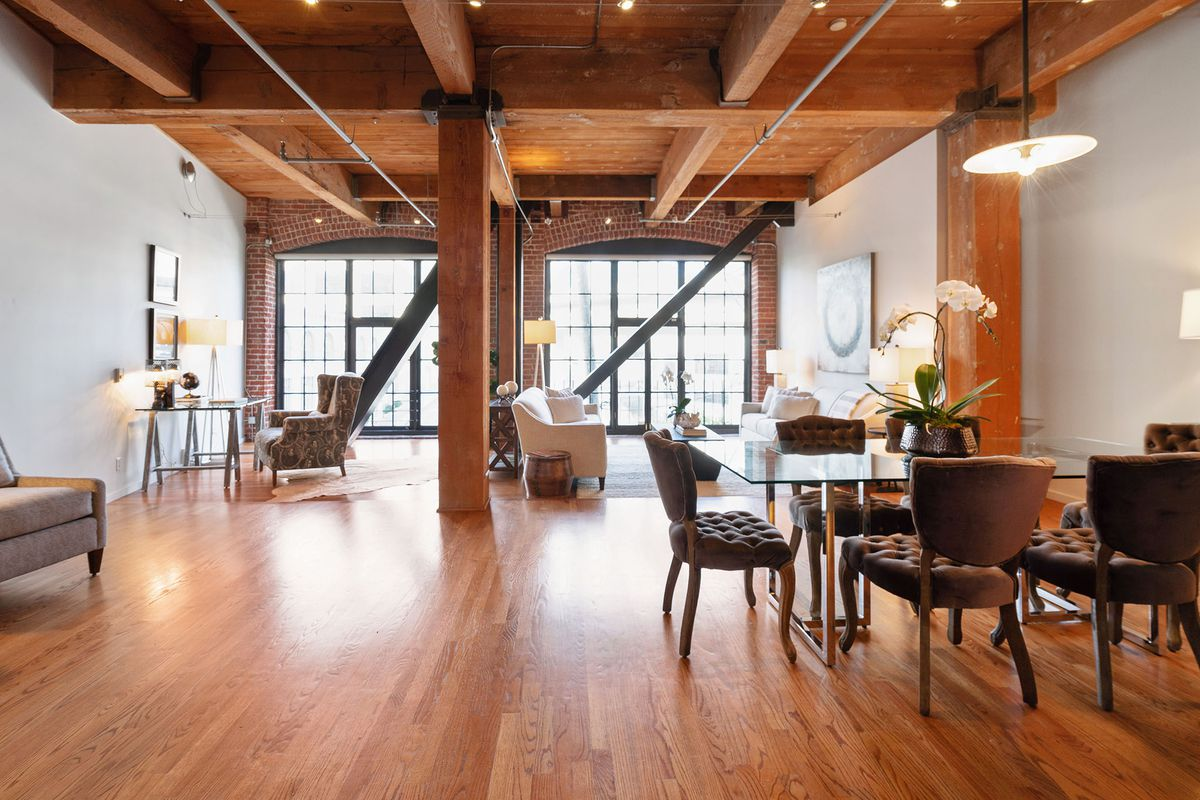 A large loft-like living room with a glass table, tufted chairs, wood floors, and an exposed wood beam ceiling.