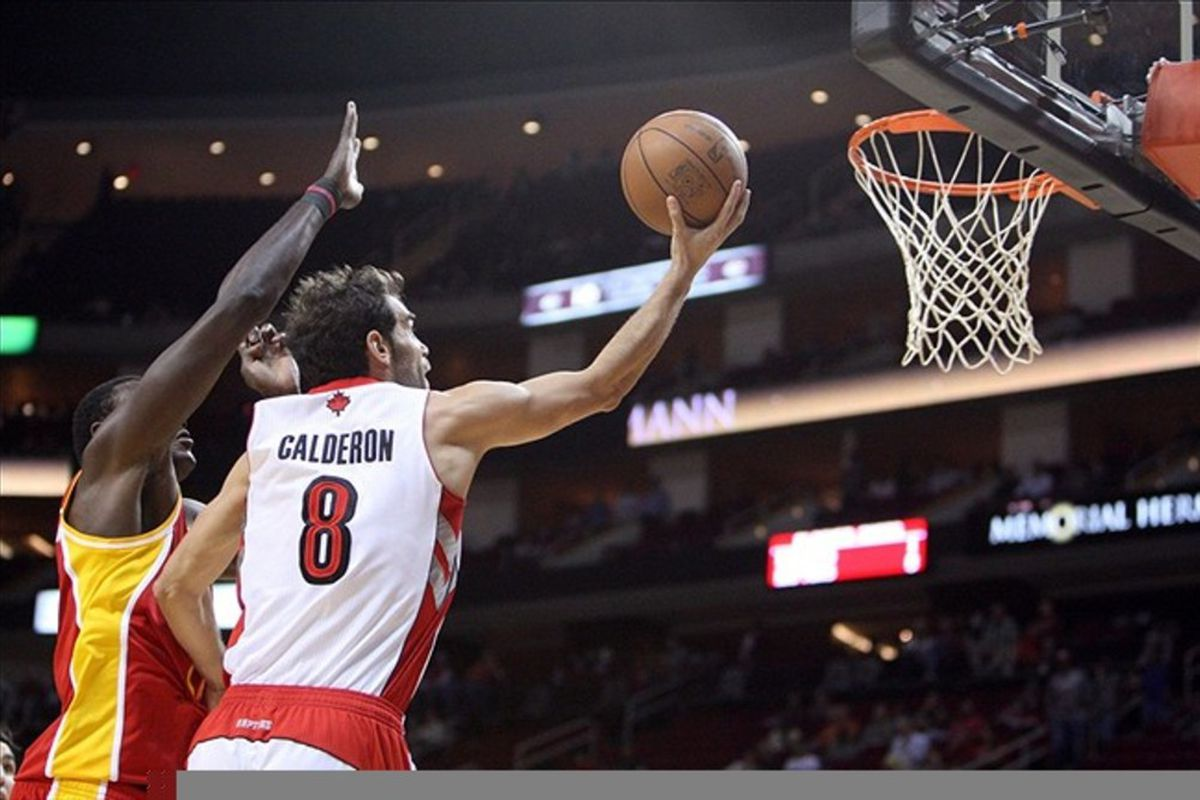 Feb 28, 2012; Houston, TX, USA; If a Calderon (8) shoots over a Dalembert (21) and no-one is there to see it, did it really happen? Mandatory Credit: Thomas Campbell-US Presswire