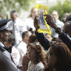 A man holds up a missing persons poster as Britain's Queen Elizabeth II and the Duke of Cambridge leave following a visit to the Westway sports centre which is providing temporary shelter for those who have been made homeless in the fire disaster in London, Friday, June 16, 2017. Relatives of those missing after a high-rise tower blaze in London are searching frantically for their loved ones, as the police commander in charge of the investigation says he hopes the death toll will not rise to three figures.