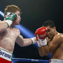 Canelo Alvarez, of Mexico, left, punches Josesito Lopez during a super welterweight championship boxing match on Saturday, Sept. 15, 2012, in Las Vegas. Alvarez won the match.