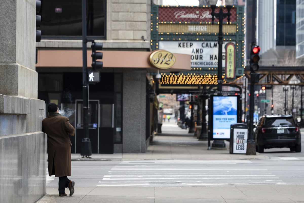 A man has the sidewalk to himself as he smokes a cigarette at the corner of Randolph and LaSalle in the Loop in March.