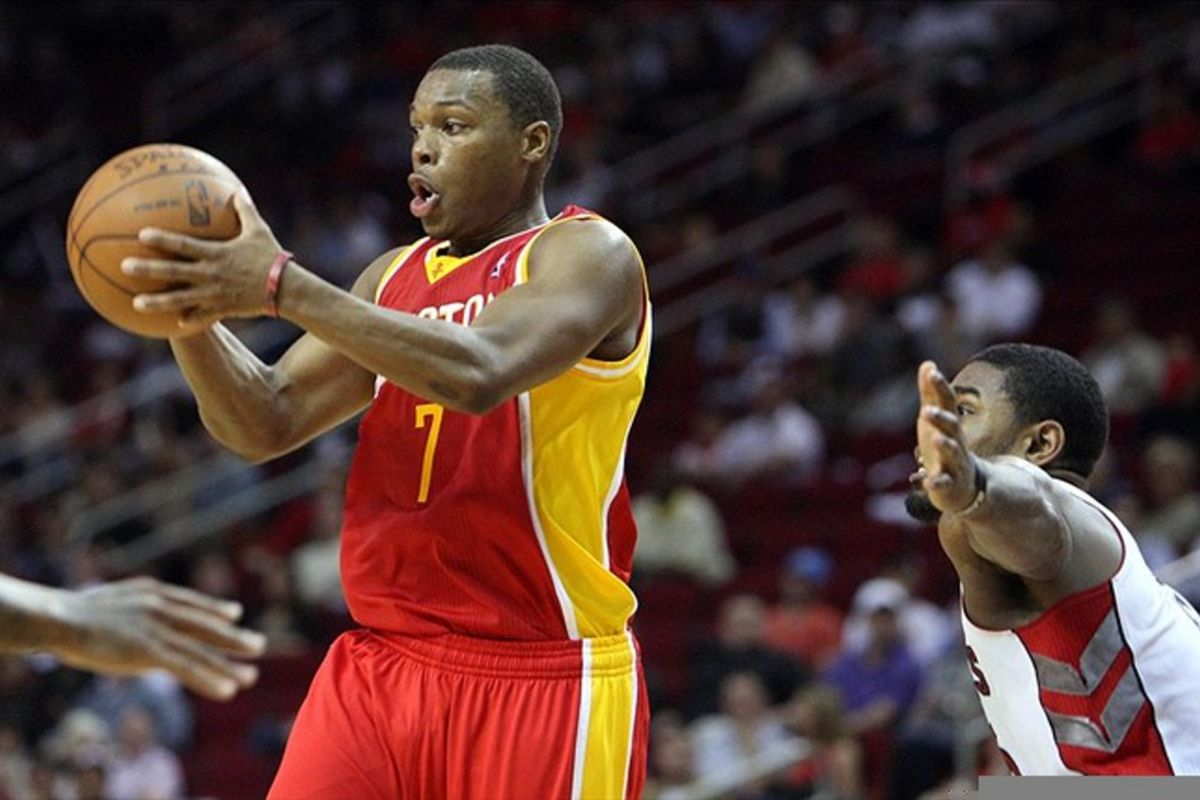 Feb 28, 2012; Houston, TX, USA; Houston Rockets point guard Kyle Lowry (7) passes across the lane against the Toronto Raptors during the third quarter at the Toyota Center. The Rockets won 88-85. Mandatory Credit: Thomas Campbell-US Presswire