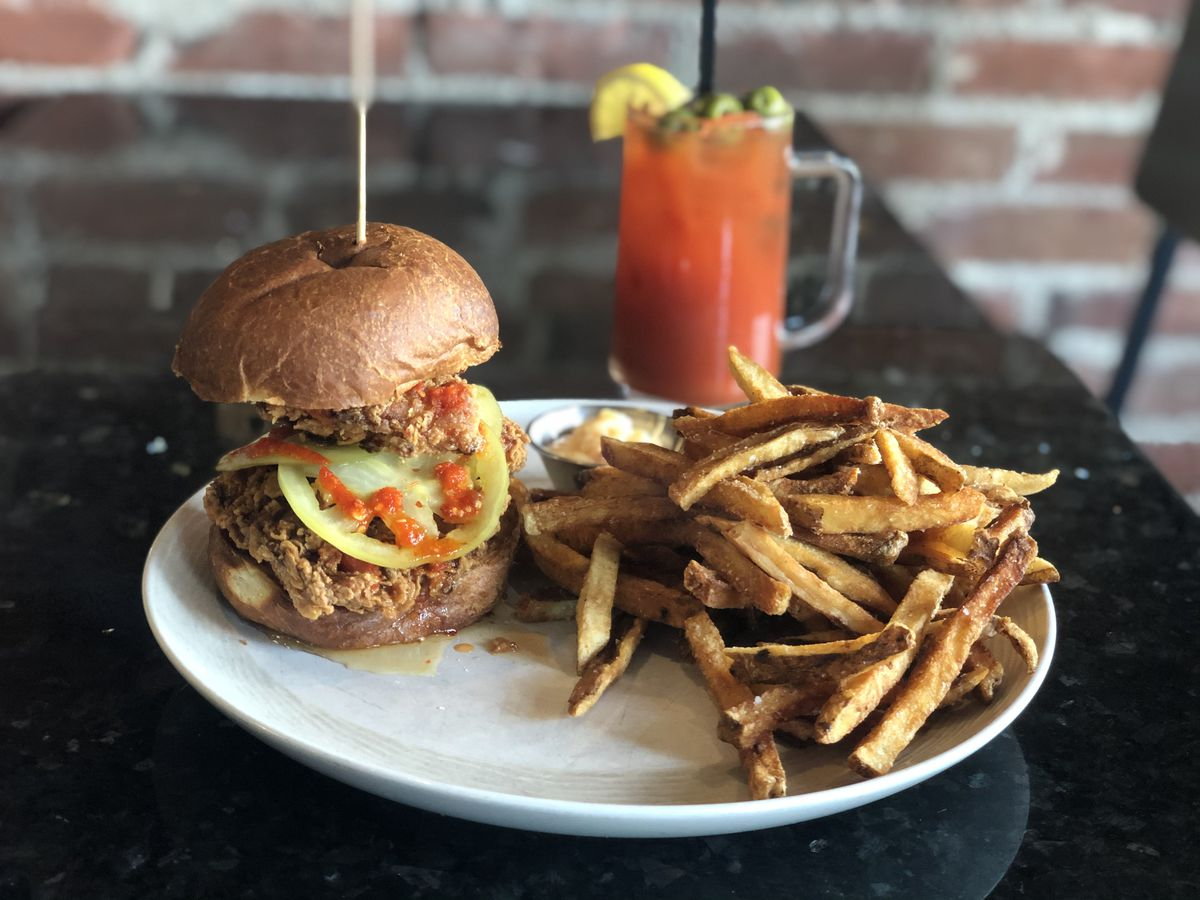 A fried chicken sandwich with a pickled tomato, side of fries, and a bloody mary sit on a shiny black restaurant table in front of a brick wall.