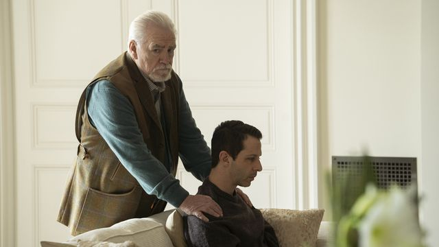 a melancholy scene on Succession: Kendall sits on a couch while his father, Logan, comforts him by putting his hands on Kendall's shoulders