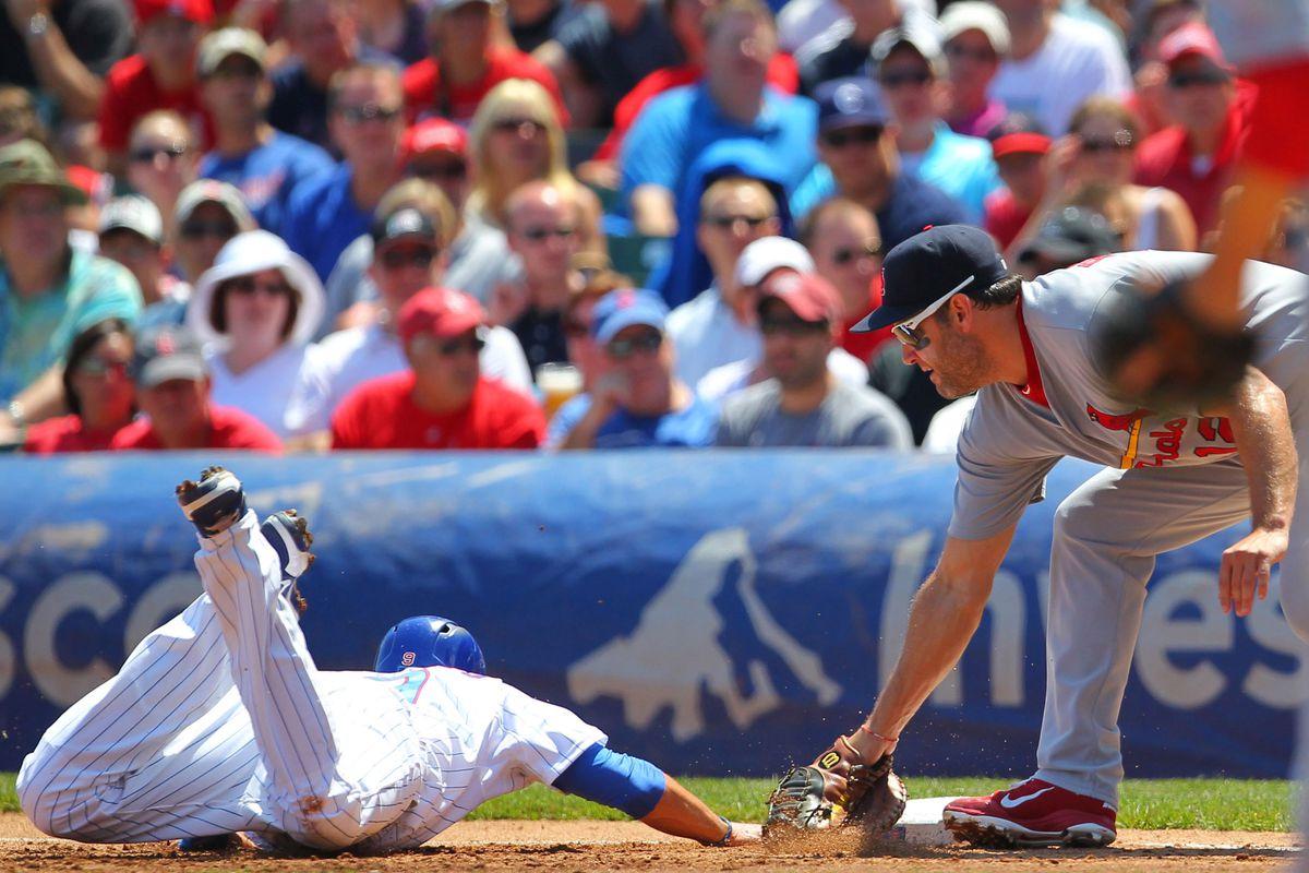 Chicago, IL, USA; Chicago Cubs right fielder David DeJesus slides under the tag of St. Louis Cardinals first baseman Lance Berkman at Wrigley Field. Credit: Dennis Wierzbicki-US PRESSWIRE