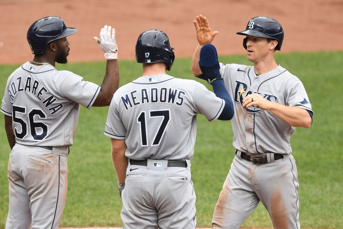 Joey Wendle of the Tampa Bay Rays celebrates with teammates Randy Arozarena and Austin Meadows after hitting a grand slam home run in the seventh inning during a baseball game against the Baltimore Orioles at Oriole Park at Camden Yards on August 29, 2021 in Baltimore, Maryland.