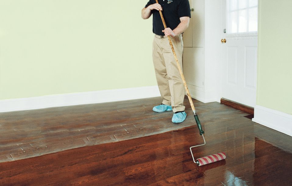 Man Using Paint Roller With Extension To Apply Polyurethane On Hardwood Floor