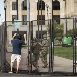 A man chats with members of the Wisconsin National Guard standing inside the barricade outside the Kenosha County Courthouse, more than a week after police shot Jacob Blake, prompting unrest in the Wisconsin city, Tuesday morning, Sept. 1, 2020. President Donald Trump is scheduled to visit Kenosha Tuesday afternoon to survey areas affected by the unrest and meet with local officials