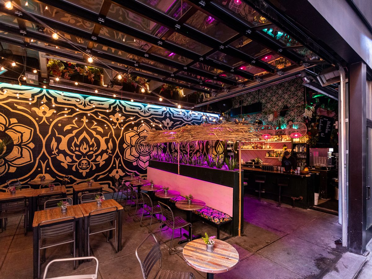 An open air bar space with art on the walls, string lights, and thatch decor.