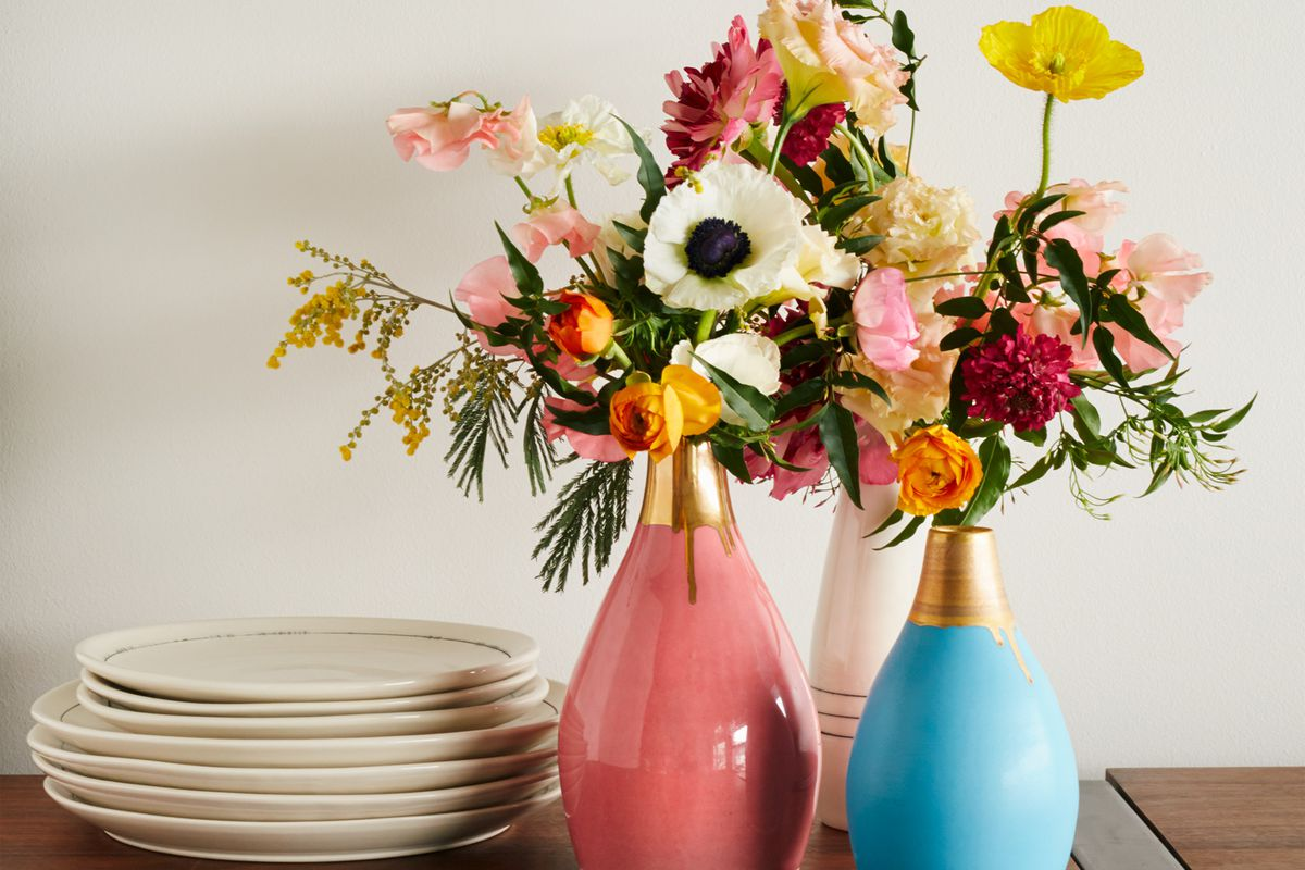 Stack of white plates next to blue and pink vases with gold on top and flowers in them