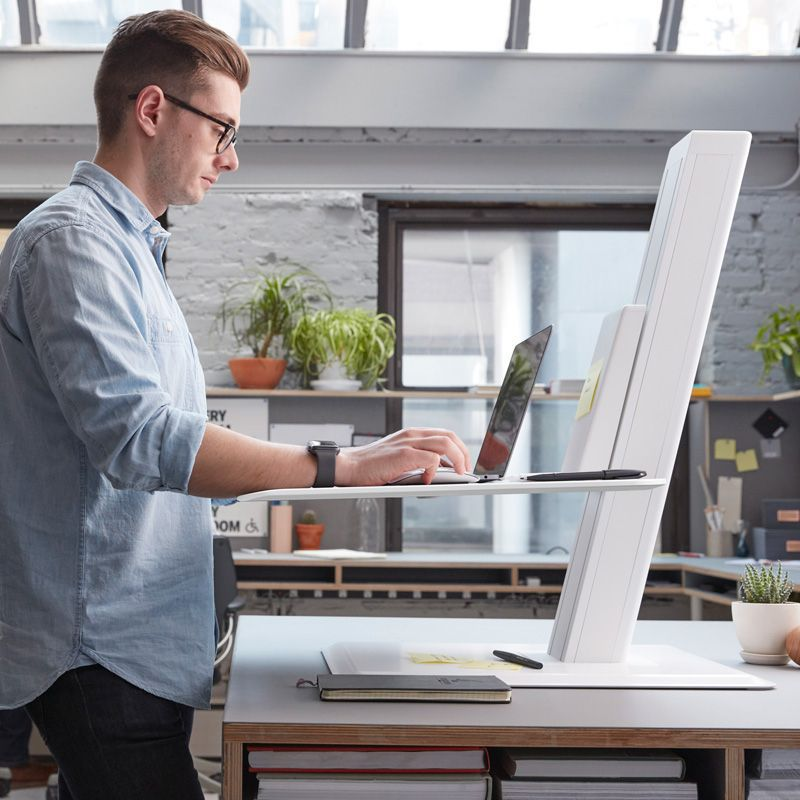 Man stands next to a desk with a smaller desk on top of it.