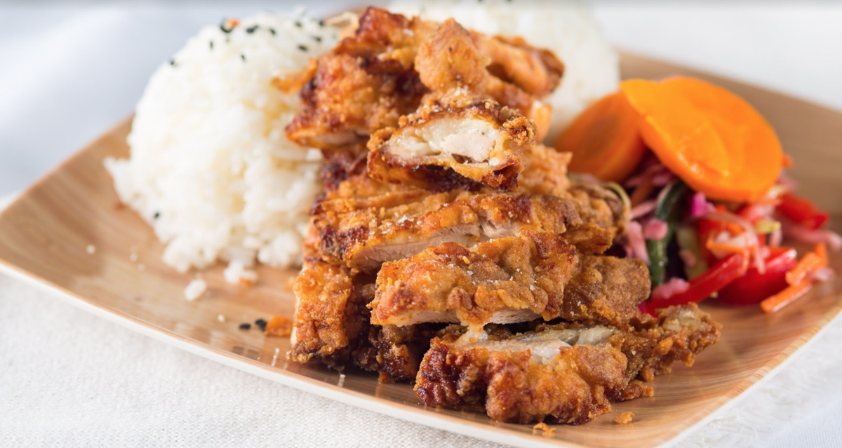 A plate of fried chicken with rice and pickled vegetables