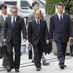 Olympus Corp.'s former President Tsuyoshi Kikukawa, front center, arrives with his lawyers at Tokyo District Court in Tokyo Tuesday, Sept. 25, 2012.  Kikukawa admitted guilt Tuesday in a cover-up scandal of massive investment losses at the major Japanese camera and medical equipment company.