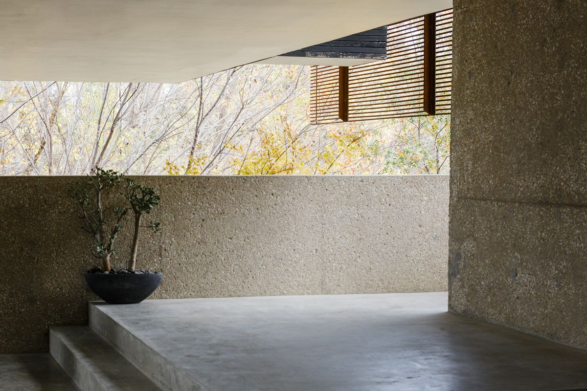 A patio is shaded by upper stories. The walls are hammered concrete.