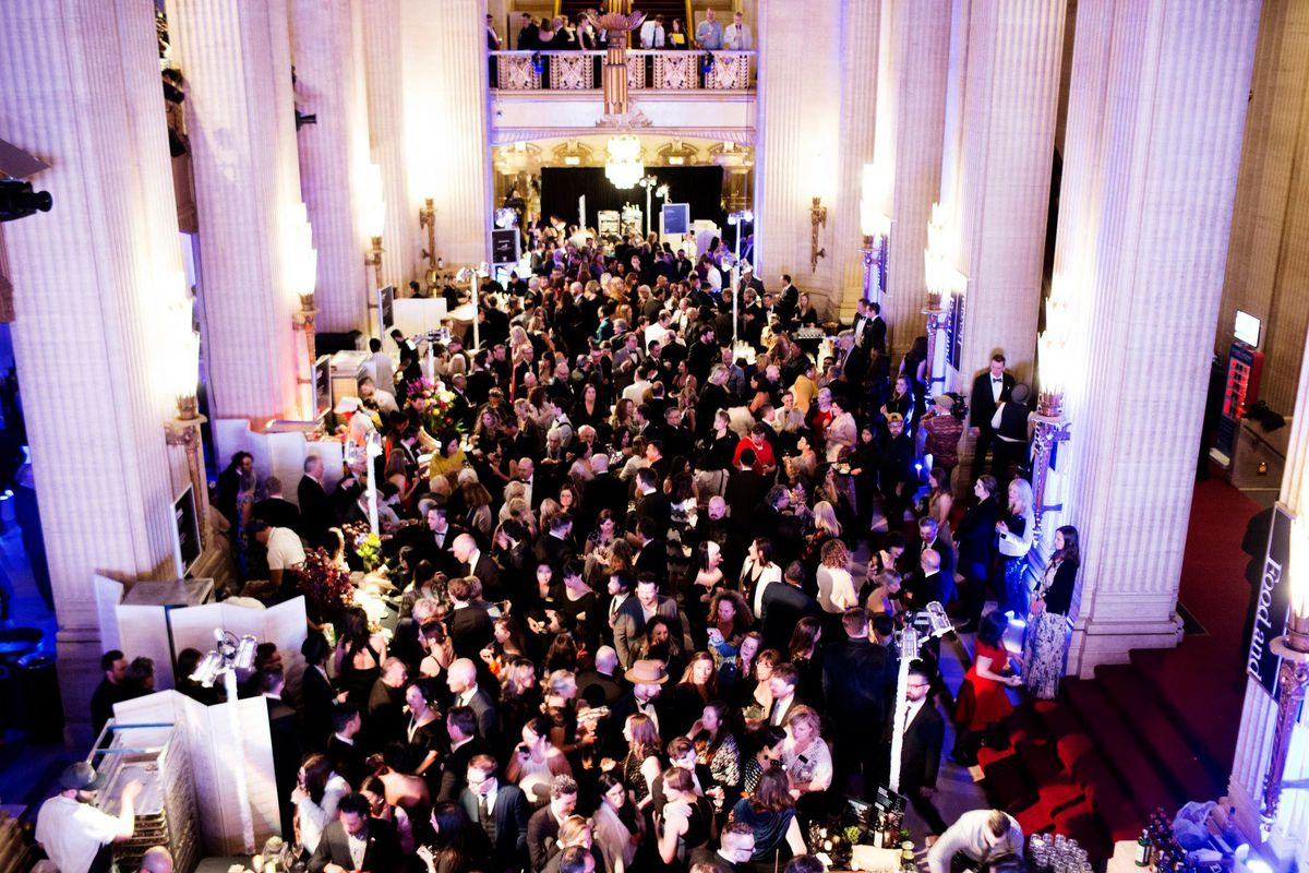 A crowd of people dressed up in black-tie outfits surrounded by high columns